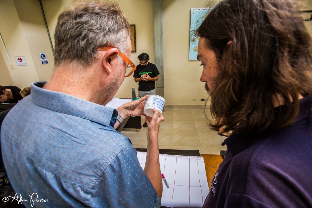 An image showing two people from behind who are looking at a detergent container as part of a garbology workshop