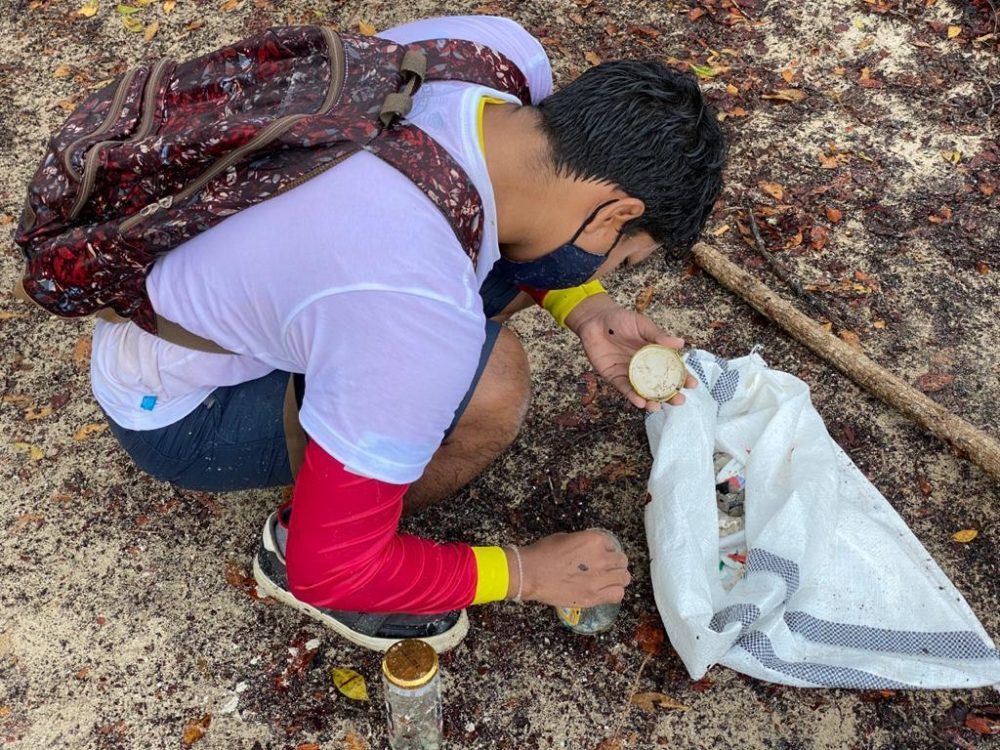A man wearing a mask is learning how to sample microplastics on a beach in Galapagos