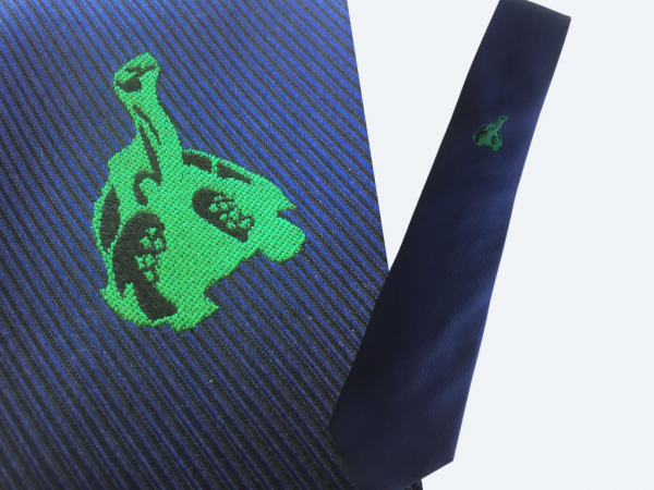 Blue silk Galapagos tie with green embroideredgiant tortoise logo