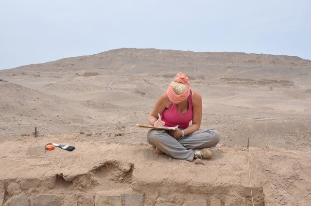 Estelle is sitting on the edge of an archaeological excavation in the desert writing on a clipboard, to her right there are some tools - a soft brush and tap measure.