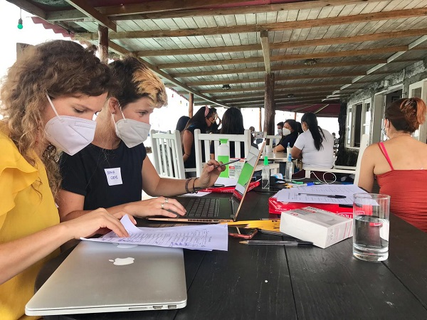 Two women are sat at a desk with laptops and face masks, behind them is a room full of people as part of a Sustainable Development Goals workshop in Galapagos