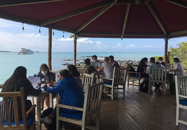 A group of people clustered around tables on an outdoor veranda with views of the ocean taking part in the Sustainable Development Workshop in Galapagos, May 2021 © Co-Galapagos